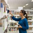Stock Photo: Girl choosing book in library