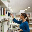 Girl choosing book in library — Stock Photo