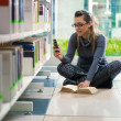 Girl text messaging with phone in library — 图库照片