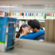 Students kissing in library — Stock Photo