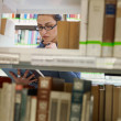 Woman choosing book in library — Stock Photo