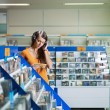 Girl listening music in cd store — Stockfoto