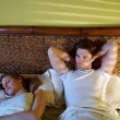 Young couple sleeping in bed - Stok fotoğraf