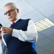 Mature businessman reading e-mails on cellphone — Stock Photo