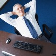 Mature businessman relaxing in office — Stock fotografie