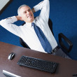 Mature businessman relaxing in office — Stockfoto