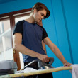 Man with iron doing chores — Stockfoto