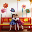 Two little girls smile and hug at school - Стоковая фотография