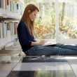 Girl studying on floor in library — Stock Photo
