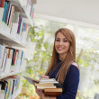 Girl choosing book in library and smiling — Stock Photo #9305169