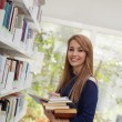 Girl choosing book in library and smiling — Stock Photo