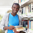 Young african man smiling in library — Stock Photo