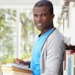 Young african man smiling in library — Stock Photo #9305172