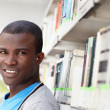 Young african man smiling in library — Stock Photo #9305174