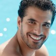 Young man sitting in swimming pool — Stock Photo