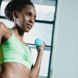 African woman exercising with small weights in gym — Stock Photo