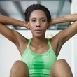 Stock Photo: African woman doing series of crunch in gym