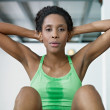 African woman doing series of crunch in gym — Stock Photo #9305662