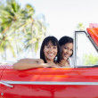 Beautiful twin sisters in cabriolet car — Stock Photo