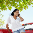 Beautiful woman on the phone near cabriolet car - Stock Photo