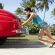 Woman pushing broken down old car - Stock Photo