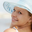Woman in straw hat smiling at camera — Stock Photo