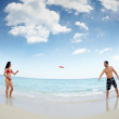Young happy man and woman playing with frisbee — Stock Photo