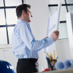 Architect reading blueprint in office — Stock Photo