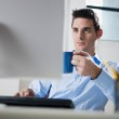 Businessman drinking coffee in office — Stock Photo