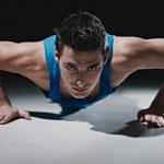 Man doing push-ups on black background — Stock Photo