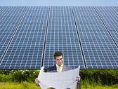 Businessman standing near solar panels — Stock Photo