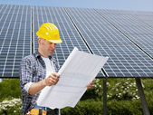 Electrician standing near solar panels — Stock Photo