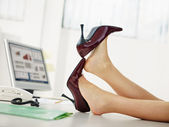 Business woman taking off shoes — Stock Photo