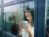 Mulher olhando pela janela — Foto Stock
