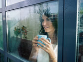 žena zíral z okna — Stock fotografie