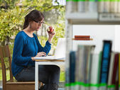 Girl holding apple in library — Stock Photo