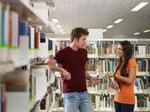 Studenti flirtování v knihovně — Stock fotografie
