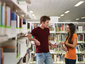 Students flirting in library — Stock fotografie