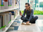 Girl text messaging with phone in library — Stock Photo