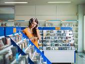 Girl listening music in cd store — Stock Photo