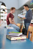 Book and notepads on desk in library — Stock Photo