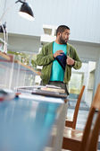 Student stealing laptop in library — Stock Photo