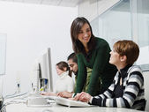 Teacher and students in computer class — Stock Photo
