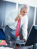 Mature businessman on the phone in office — Stock Photo
