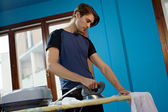 Man with iron doing chores — Stock Photo
