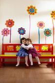 Dos niñas sonrían y abrazan en la escuela — Foto de Stock