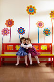 Two little girls smile and hug at school — Stock Photo