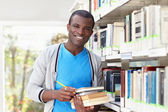 Young african man smiling in library — Φωτογραφία Αρχείου