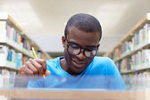 Young african man studying in library — Stok fotoğraf