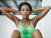African woman doing series of crunch in gym — Stock Photo